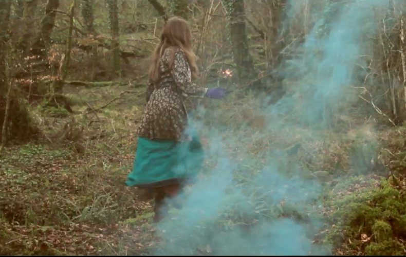 Jess in the woods with a blue smoke bomb