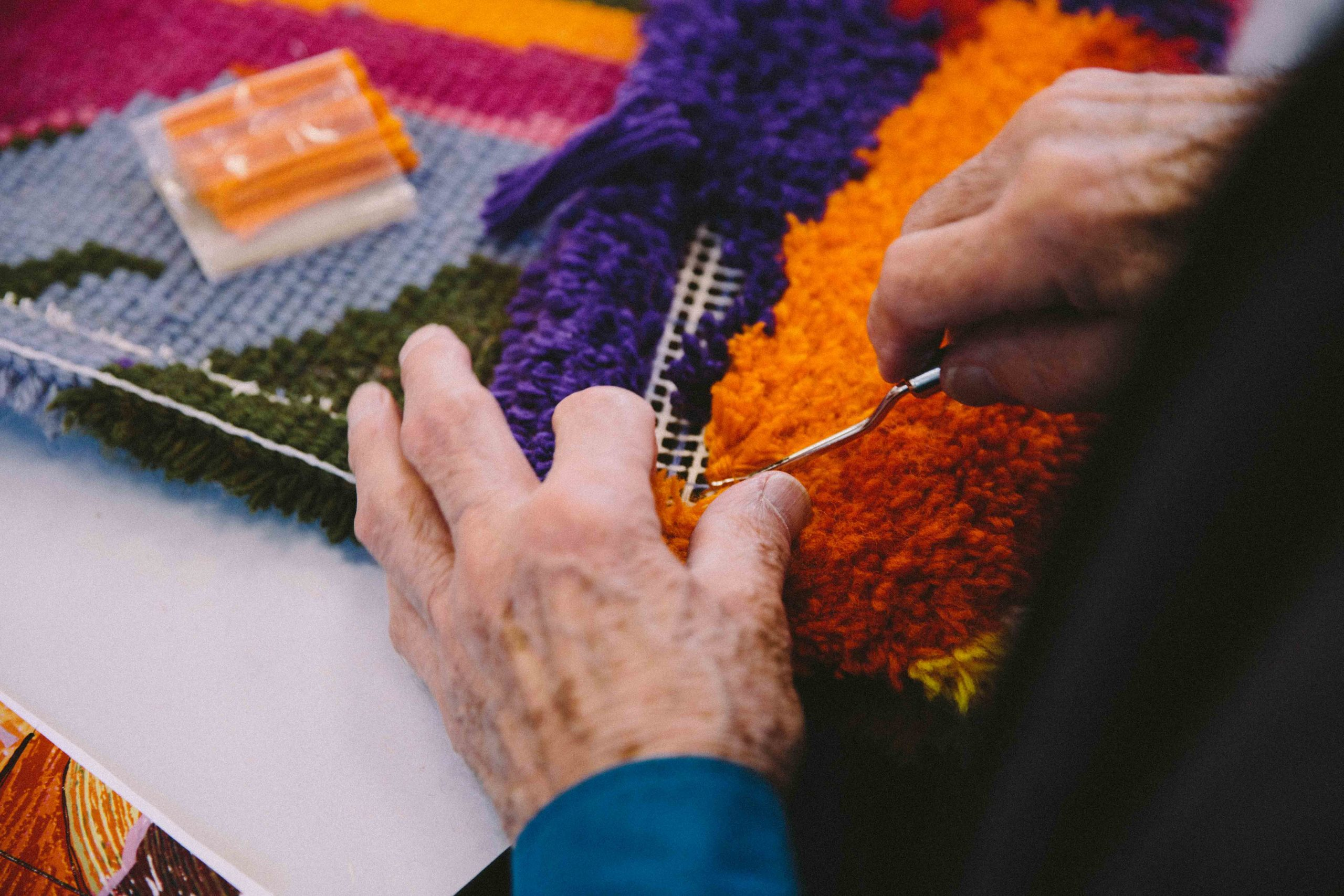Keith Gretton's hands with colourful wool