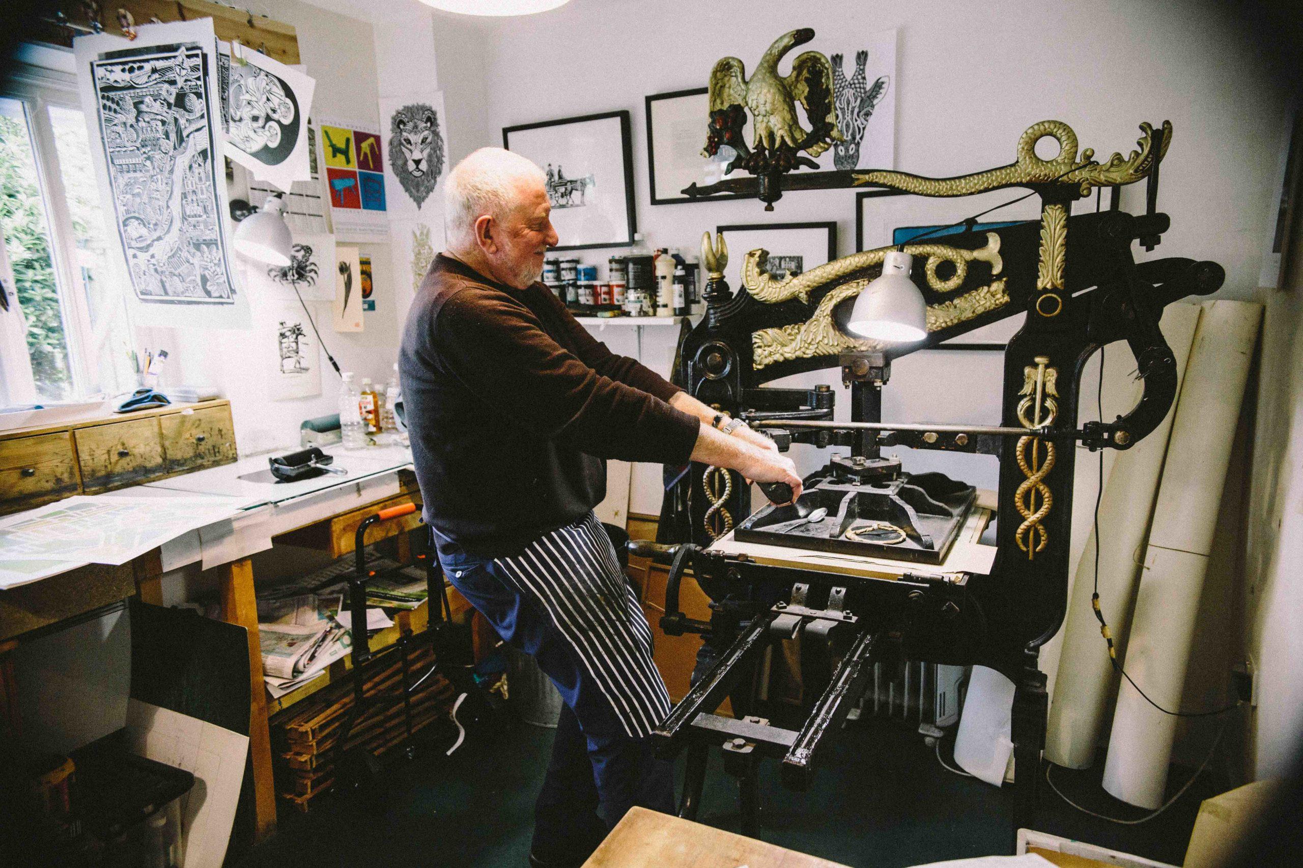 Hugh Ribbons pressing a lino cut