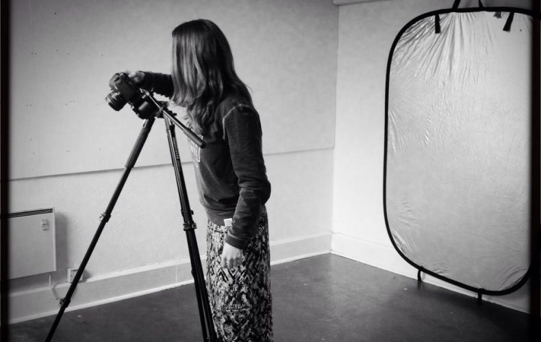 Black and white photo of Jess filming with a camera and tripod