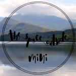 The Space Outside Mini Logo in front of a lake